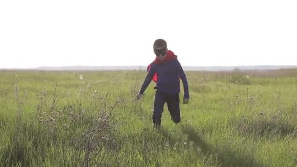 fiú szuperhős egy mezőben a naplemente