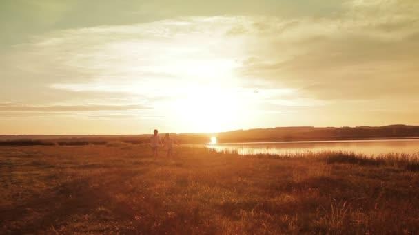 Dva kluci běží na pláži při západu slunce