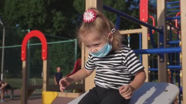 Das kleine Mädchen trägt eine medizinische Schutzmaske auf dem Gesicht. Kinder spielen draußen im Kinderpark. Konzept der Sicherheit von Kindern vor einer Infektion. Mädchen wird im Park mit Schutzmaske geschützt.