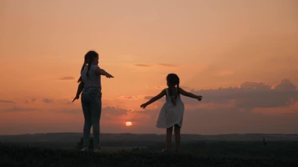 Silueta šťastné rodiny při západu slunce v parku. Dvě školačky se drží za ruce a sní. Šťastné děti mávají rukama. V parku se rýsuje obrys školaček. Šťastné děti sní