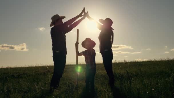Týmová práce. Šťastný rodinný otec, matka a syn sní o vlastním domově - o symbolu budoucího bydlení. Šťastná rodina se při západu slunce drží za ruce. Otec, matka a syn týmová práce. Sen o domově