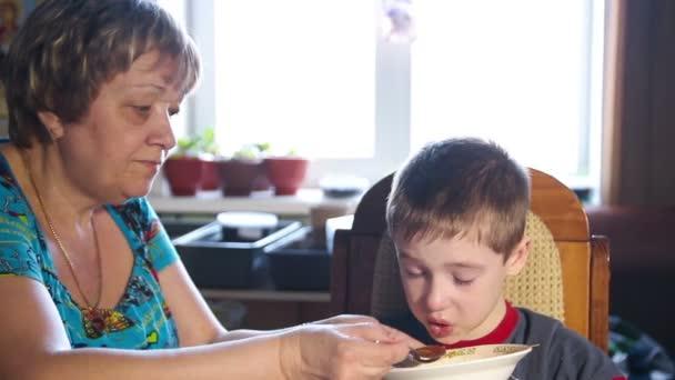 primo piano di una donna che alimenta il pranzo ragazzo, deliziosa zuppa, famiglia felice, video 1080p
