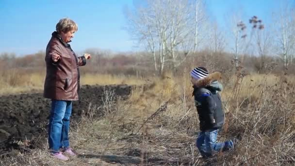 Happy grandson hugging grandmother over a nature outdoor background. video HD 1080p