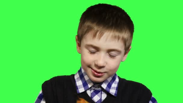 Cheerful boy close-up eats a pear on a green background, 1080p HD video