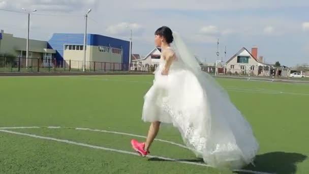 mladí Svatební pár hrát fotbal na zelené louce