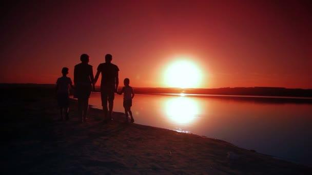 rodina 4 osoby na pláži, drželi se za ruce na slunce silueta jezero, vodě a pískové teplý a krásný večer, 1080p video