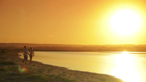 Two boys dressed in white running along the shore of the lake on the background of the water and sunset silhouettes