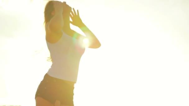 Krásná mladá dívka narovná dlouhé vlasy, pohybující se ve větru při západu slunce, teplé letní večery
