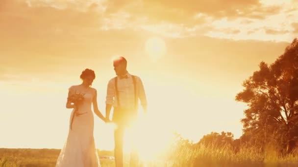 Fiatal gyönyörű és a boldog pár menyasszony és a vőlegény, séta a naplemente, esküvő napján