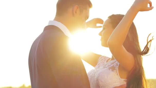 Young couple in love bride and groom on the background of sunset, straightens hair backlight, field of wheat, soft and romantic, white dress, tie.