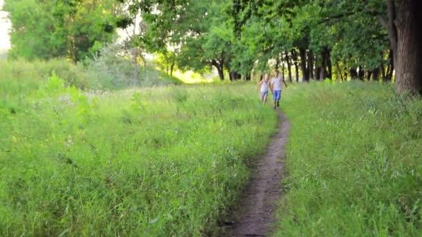 dva chlapci v bílých šatech, v parku, drželi se za ruce smějí a mají zábavu
