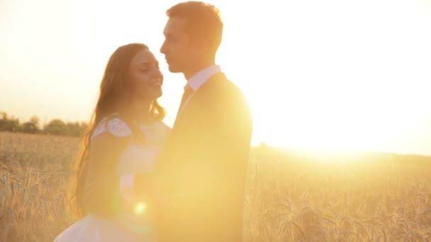 Gyönyörű fiatal pár menyasszony és a vőlegény egy esküvői ruha a naplemente egy Búzamező, kézen