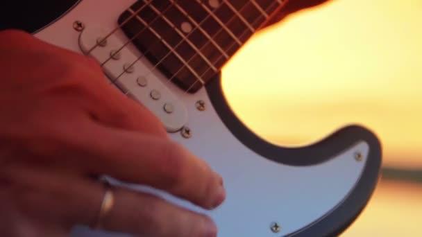 Muž close-up elektrická kytara hrát rock při západu slunce a jezero