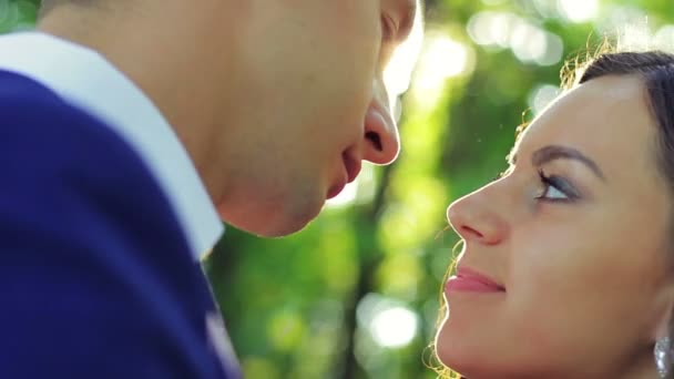 Gyönyörű fiatal pár menyasszony és a vőlegény egy esküvői ruha a napfényben, gyöngéden néztek egymásra, csók, boldog család, szerelem