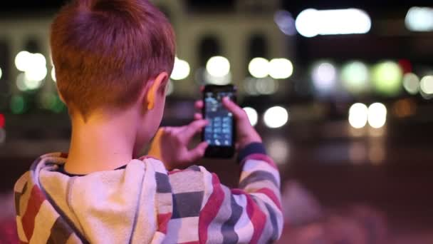 Smartphone man calling on mobile phone at night in the city. Handsome young boy says to a smartphone smiling happy outdoors.
