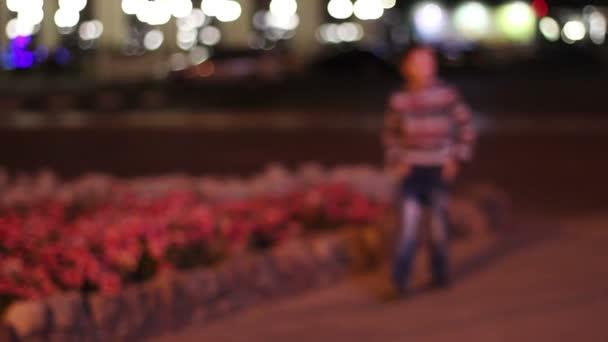 Malý chlapec 8 let, vhodné pro kamery je ve vzduchu město v noci a čtení zářící reklamy