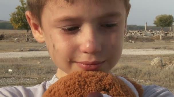špinavý malý sirotek detail pláč a mazlení vycpané hračky utírá slzy na pozadí trosek zničených domů
