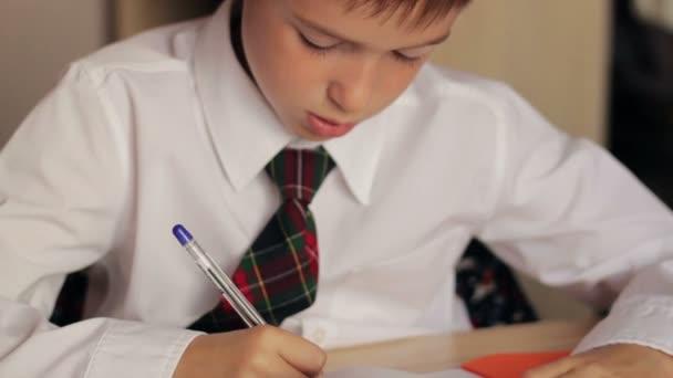 Malý chlapec detail školák v bílé košili a kravatě dělat domácí úkoly, sedí u stolu a píše perem notebook
