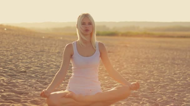 Young beautiful girl in white clothes doing yoga on the shore of the lake  at sunset  sitting on the sand