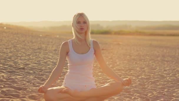 junges schönes Mädchen in weißen Kleidern beim Yoga am Ufer des Sees bei Sonnenuntergang im Sand sitzend