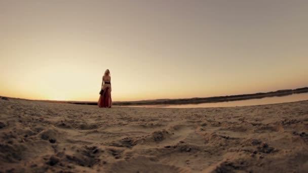 Szexi szép lány modell séta a tengerparton napnyugtakor a nap a ruha