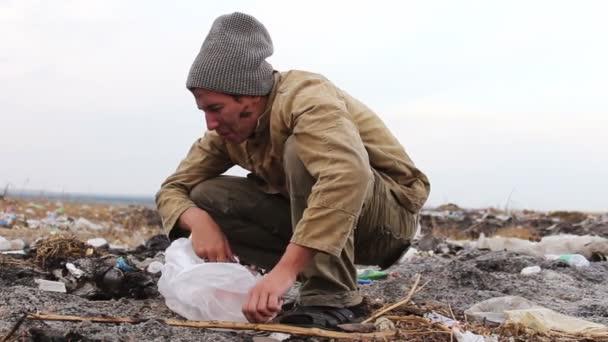 dreckiger Obdachloser sitzt auf einer Nahaufnahme des Mülls und isst unterwegs das Brot eines Videopakets