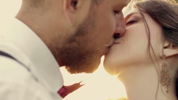 mladý pár krásná nevěsta a ženich líbat v parku při západu slunce slunce