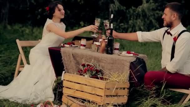 gyönyörű fiatal pár menyasszony és a vőlegény, pohár bor egy asztalnál, a Park, naplemente, romantikus vacsora