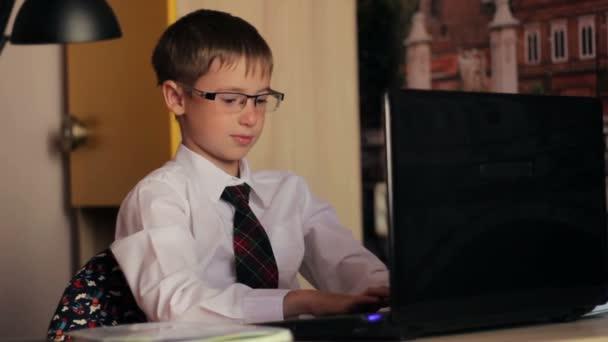 Chlapec s brýlemi, pracují na přenosném počítači. Mladý muž ví, jak zacházet s technologií hračky, koncepce vzdělávání, školení, Internet, domácí úkoly a sociální média