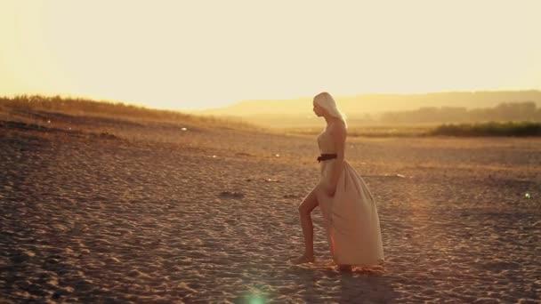 junge sexy schöne Mädchen mit langen Haaren in einem schönen Kleid spaziert am Strand bei Sonnenuntergang Kleid entwickelt sich im Wind