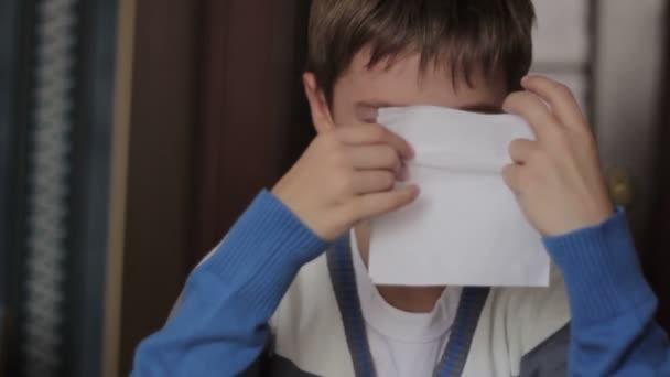 Kranken jungen beim Sitzen an einem Tisch zu Hause seine Nase weht