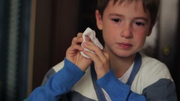 kranker Junge pustet seine Nase in Serviette, während er zu Hause am Tisch sitzt