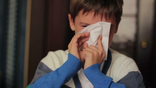 Sick boy foukání nosem do ubrousku sedíte u stolu doma