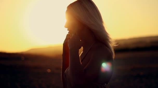 Krásná mladá sexy dívka záběr na západ slunce narovnává dlouhé bílé vlasy a dýchat čerstvý vzduch