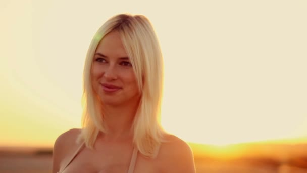 Young beautiful sexy girl at sunset closeup corrects long white hair and breathe the fresh  air, yellow desert sand
