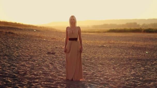 Mladá svůdná žena s dlouhými vlasy v hezké šaty stojící na pláži při západu slunce, žlutá pouštní písek