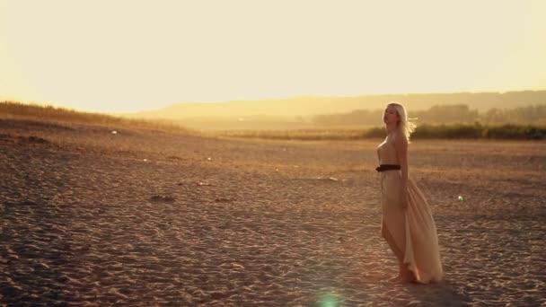 junges schönes Mädchen mit langen Haaren in einem schönen Kleid, das bei Sonnenuntergang auf dem Sand spaziert, gelber Wüstensand