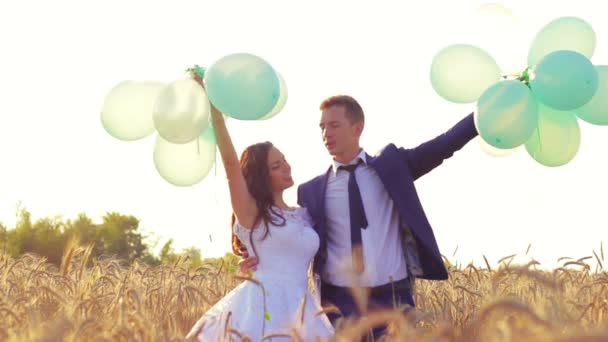 Wedding couple hugging and kissing outdoors in a field with balloons. Bride and groom standing in the grass of wheat.