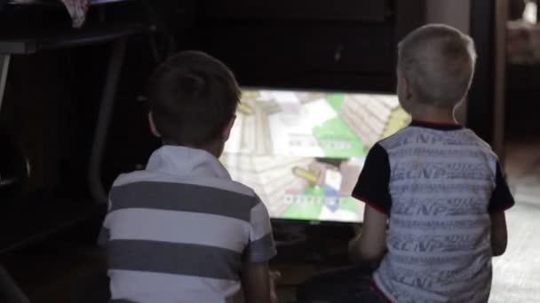 dva chlapci hrají počítačové hry sedí doma