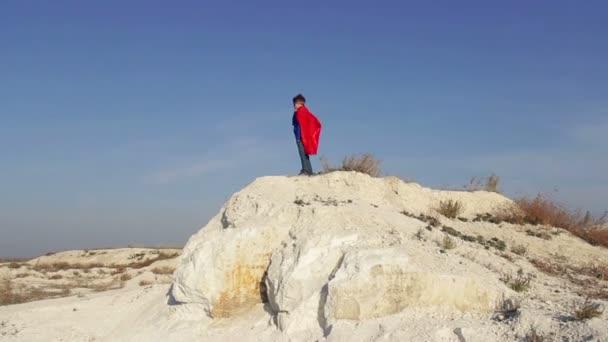 ragazzo del supereroe viene eseguito attraverso le montagne e cercando di volare