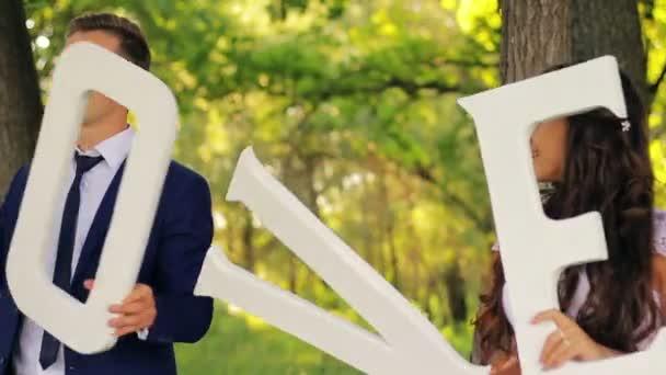 krásný mladý pár, nevěsta a ženich v parku, se slovo láska, tanec, bílé šaty, oblek, kravata, něhu, romantiku a zábavy, video 1080p