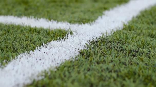 Nahaufnahme weißer Markierungen auf dem grünen Fußballplatz in Bewegung im Freien