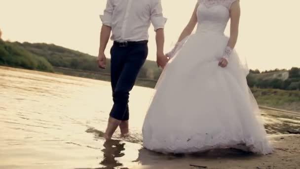 nevěsta a ženich chůze naboso na okraji čisté vody při západu slunce