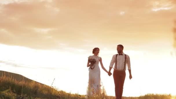 menyasszony és a vőlegény kezét sétál a naplementében