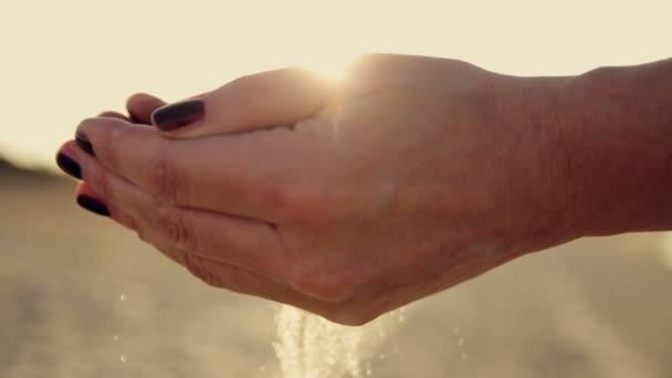 Ženská ruka bodový písek při západu slunce