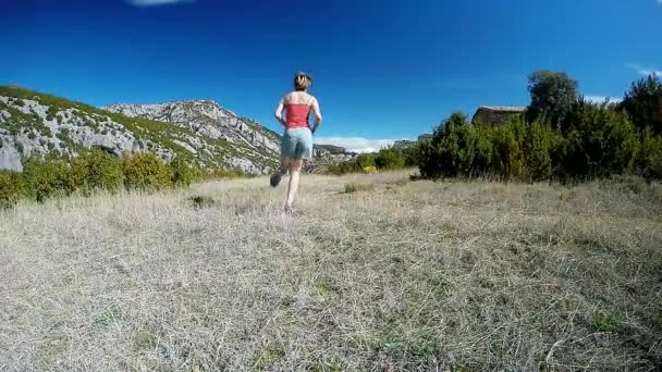 young woman running away on mountain trail in alpine meadow