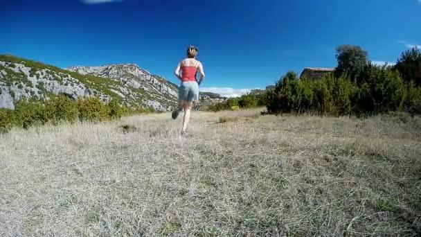 mladá žena, utíkat na horské stezce na alpské louce