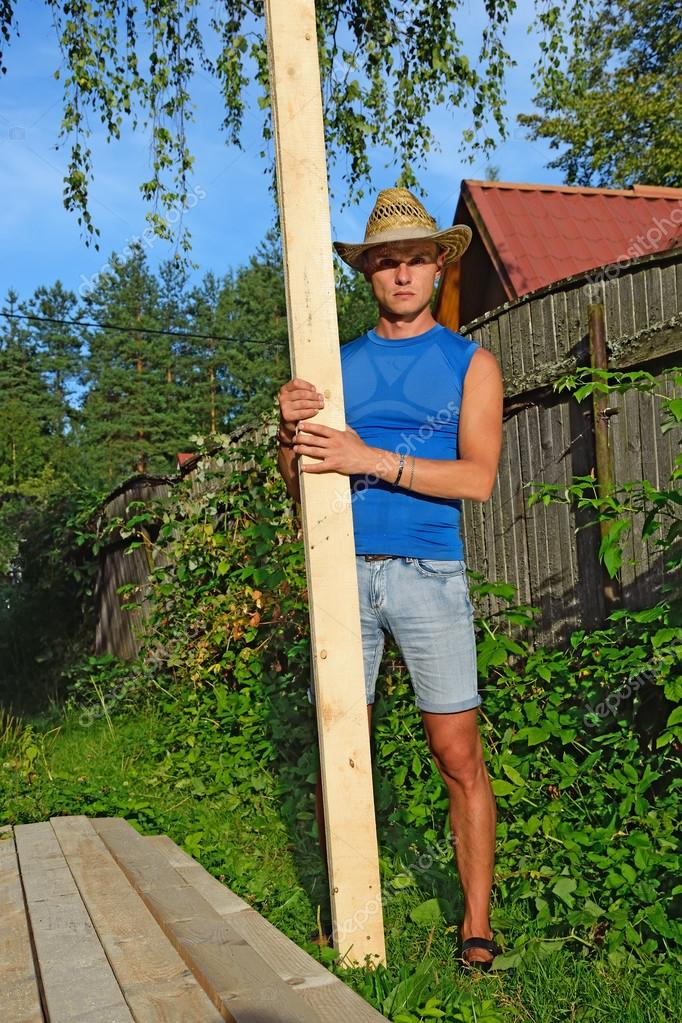 A young man with the pine Board in the hands of about a pile of boards on the plot in the summer on a Sunny day