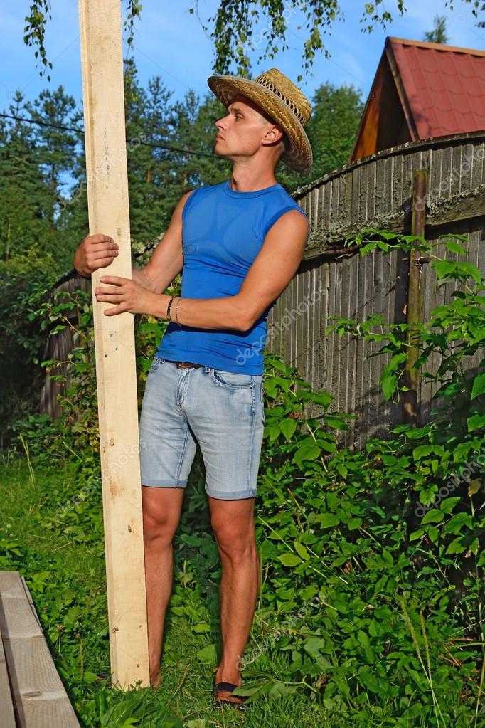 Young handsome man looks at a pine Board in the hands of about a pile of boards on the plot in the summer on a Sunny day