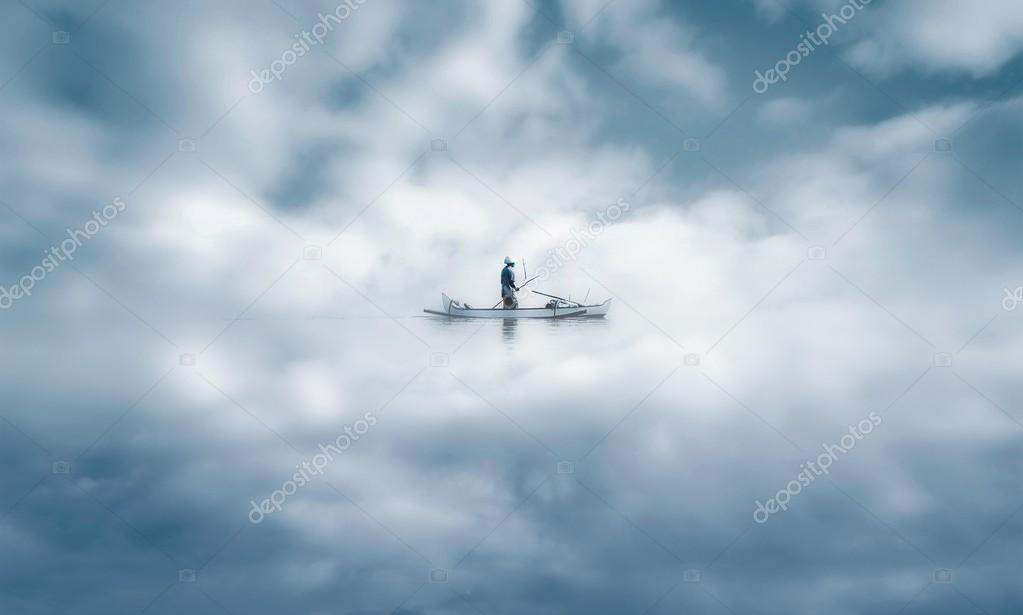 Fisherman with his small boat in a misty morning